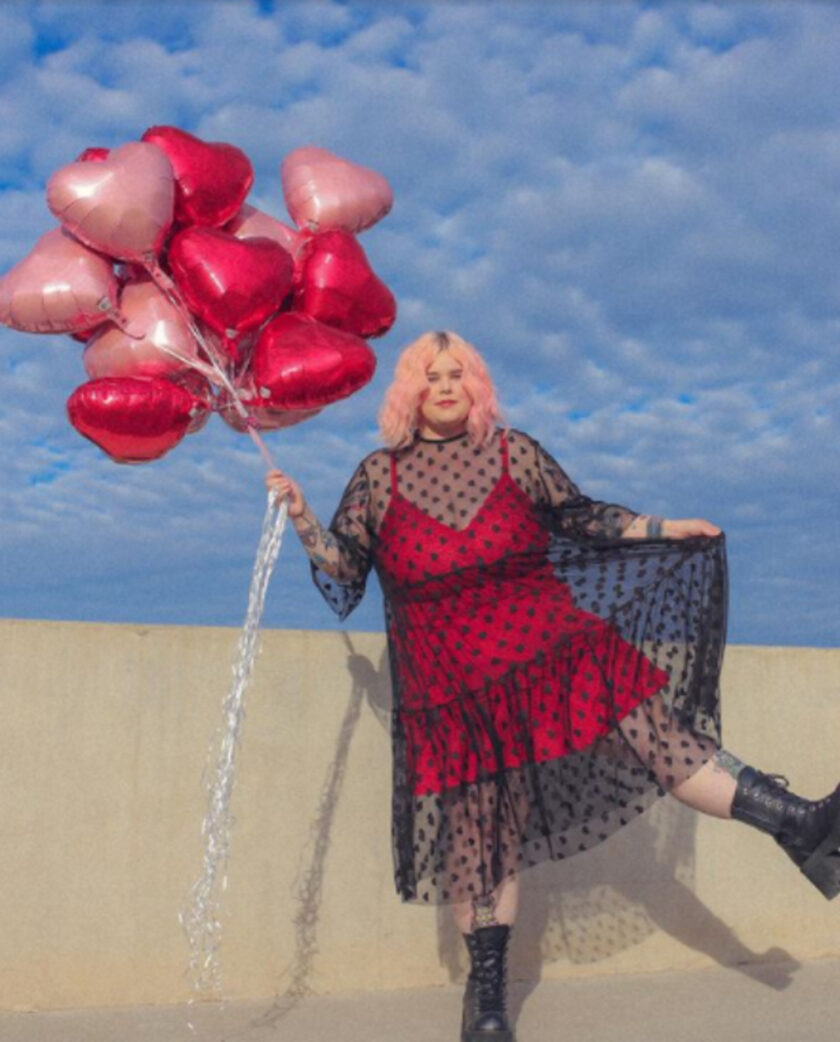 Caelyn in a red dress with black mesh holding heart shaped balloons